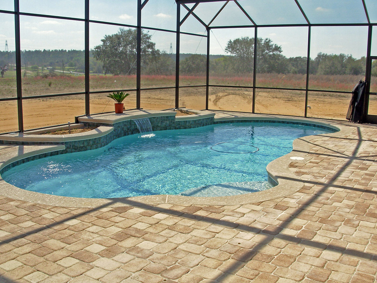 Swimming pools with water feature design ideas - Installing pavers around swimming pool ...